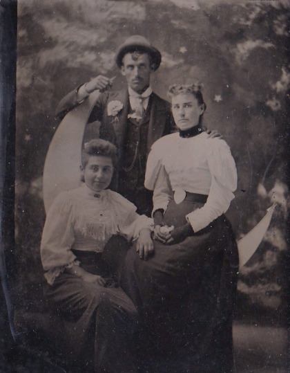 Tintype, 1890s. Note the tiny details on this one: the woman's black mitts, the painted sky background, how the man holds on to the top of the moon.